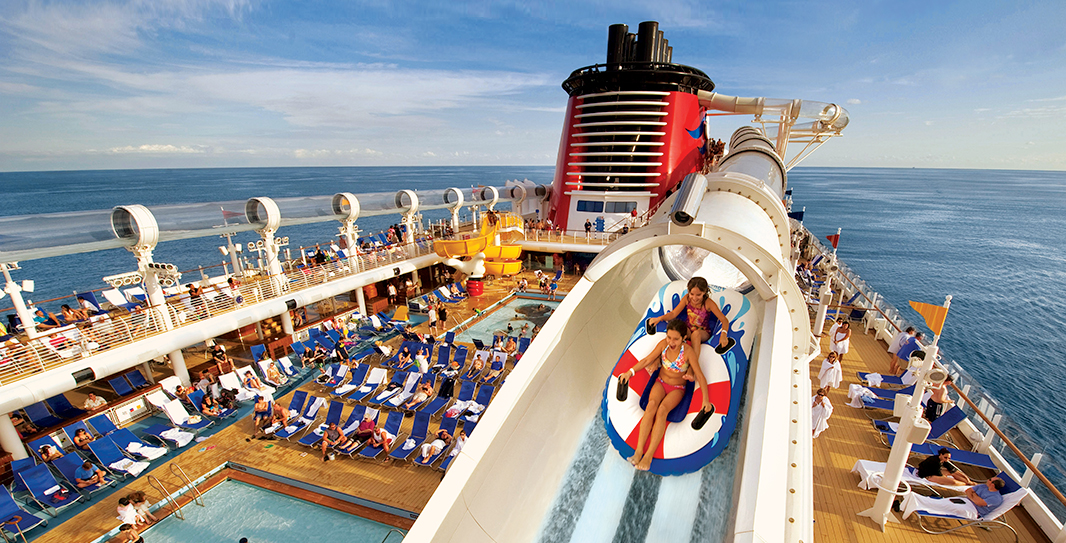Two girls in colorful inflatable tubes ride a waterslide built high above a cruise ship's deck, which is lined with Guests in lounge