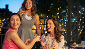 Three women enjoy drinks and appetizers at an outdoor table