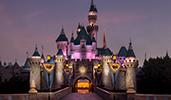 Lights illuminate Sleeping Beauty Castle in Disneyland Park at sunset