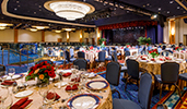 A formal ballroom with a stage area and dozens of fully set tables and chairs