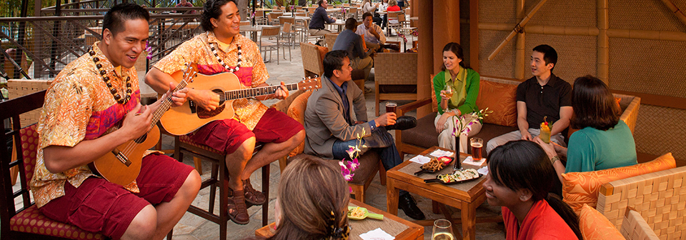 People sit at a restaurant while 2 men play a ukulele and a guitar nearby