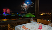 A restaurant table with a view of fireworks erupting over Magic Kingdom Park