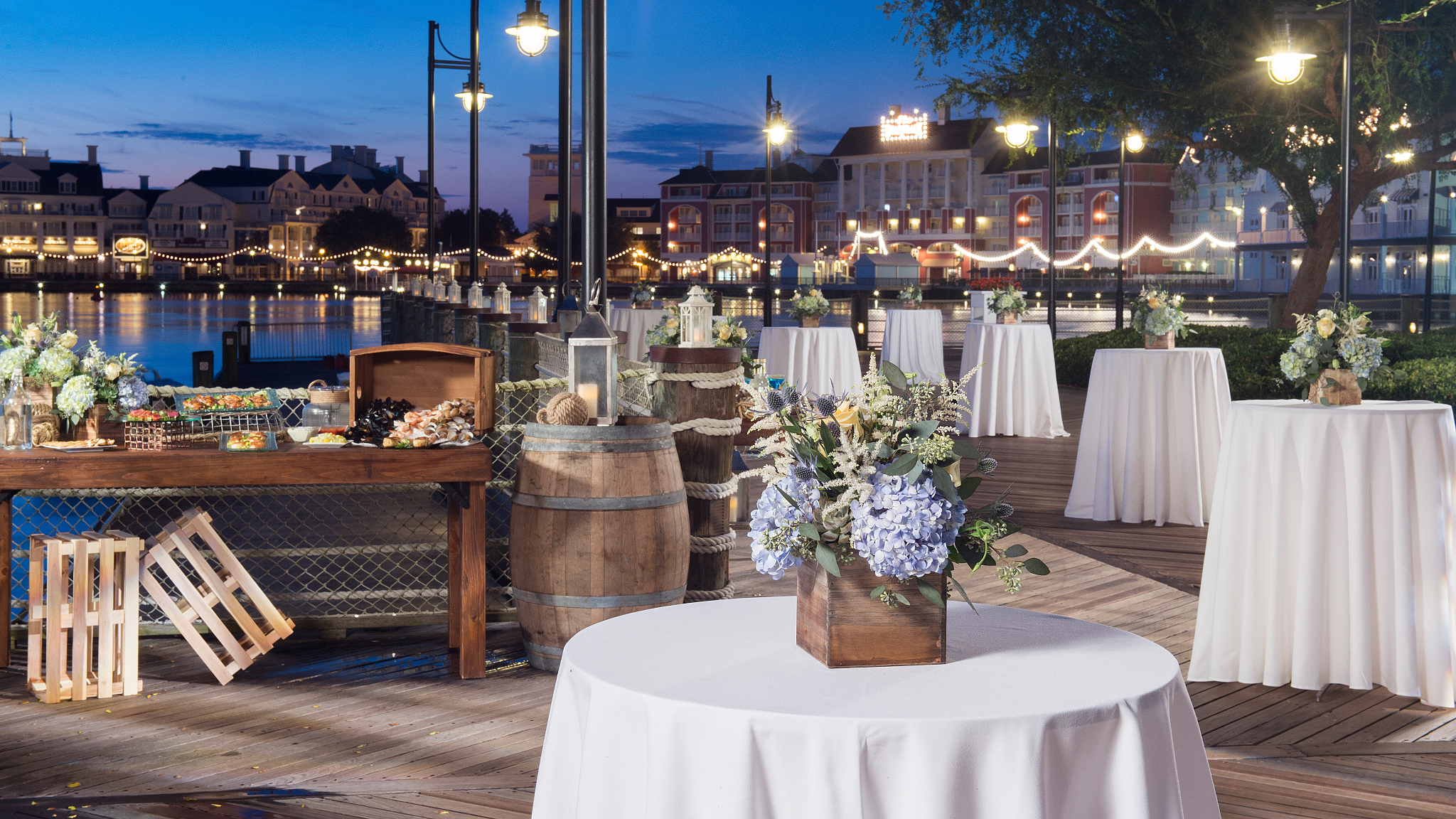 A boardwalk overlooking a lake featuring high tables with linens and floral centerpieces