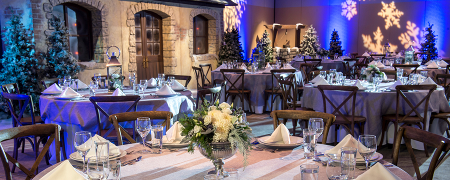 A room with winter decorations including snowflake light projections, pine trees and dining tables featuring linens, floral centerpieces and more