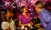 Smiling people watching fireworks in the evening sky at an area by the water with round high bar tables featuring refreshments