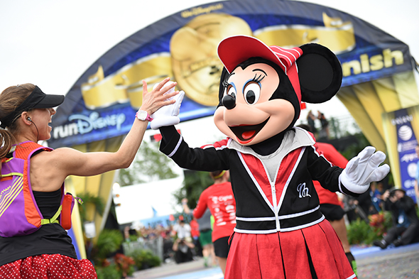 Runner high-fives Minnie Mouse at the finish line of the Walt Disney World Marathon.