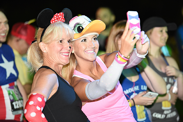 Mother and daughter dressed as Minnie Mouse and Daisy Duck get ready for the Disney Wine & Dine Half Marathon at Walt Disney World