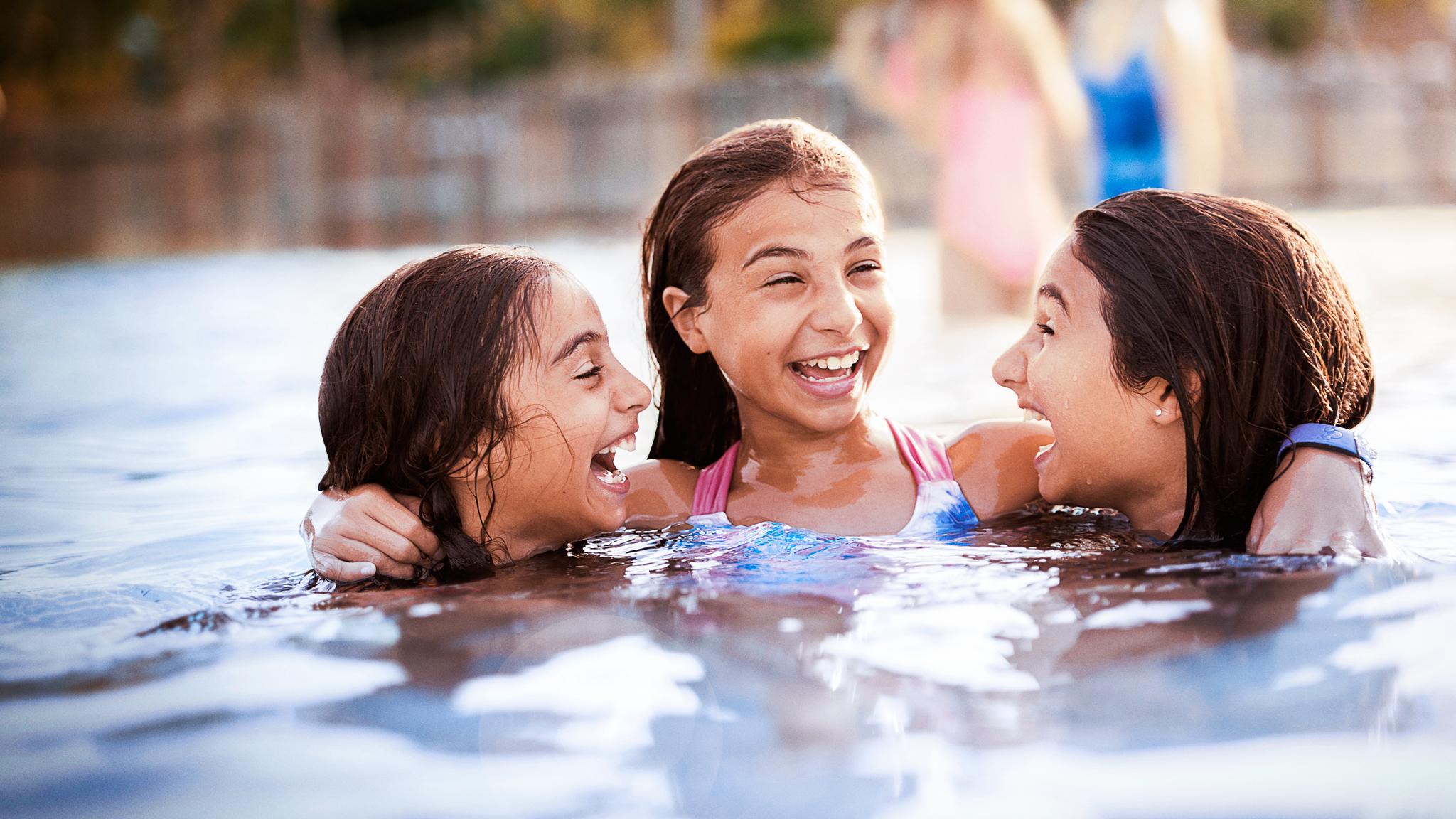 Three tween girls hang out in a pool at their Walt Disney World Resort hotel