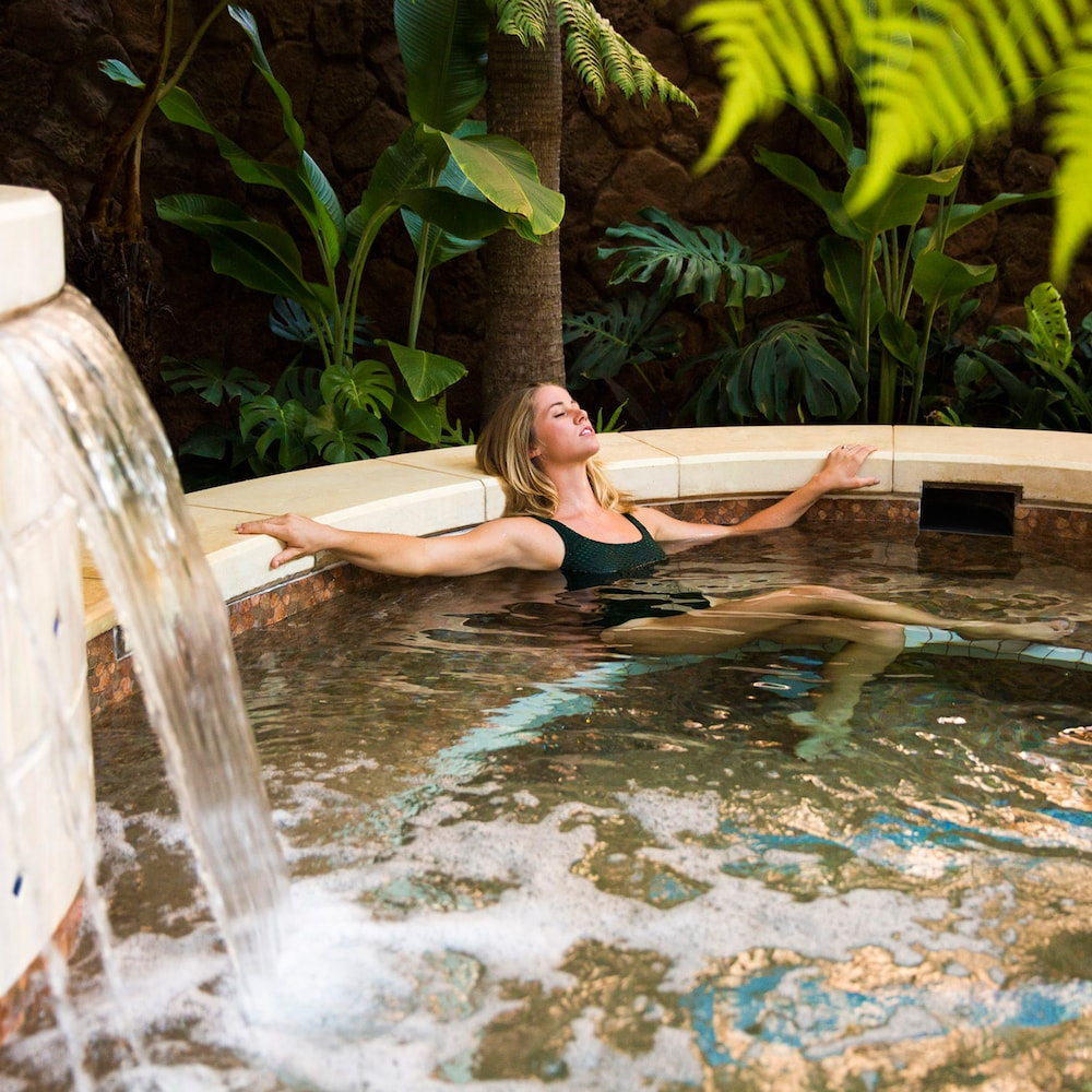 A woman relaxes while soaking in an outdoor bath at Laniwai Spa