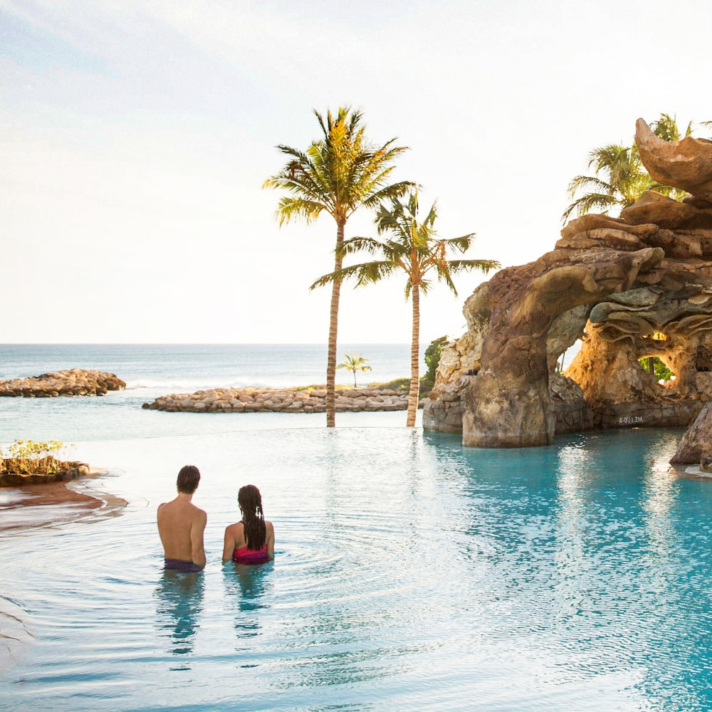 カ・マカ・グロットの海に面したプールで海を眺めながらリラックスするカップル