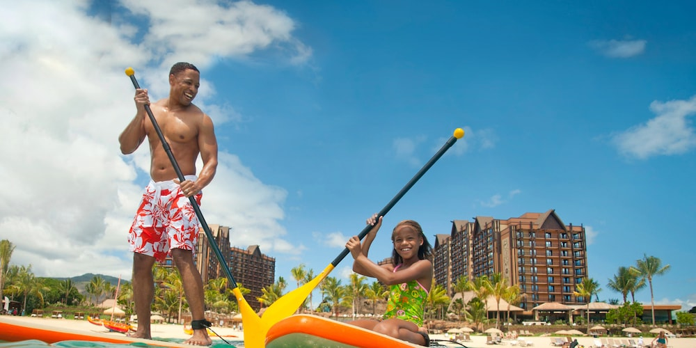A father stands on a paddleboard next to his daughter, who is kneeling on a paddleboard, on the ocean in front of Aulani Resort
