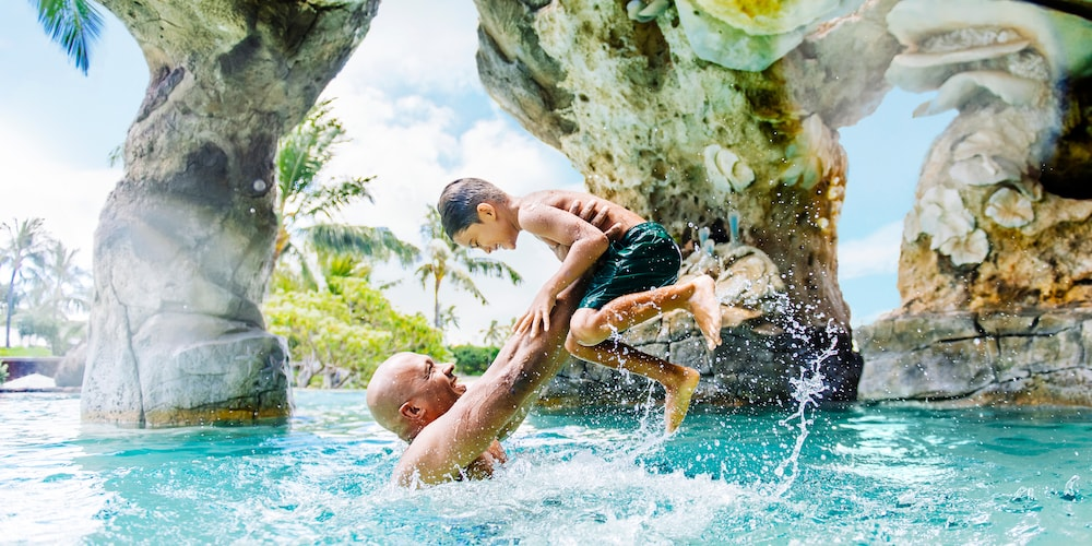 A father and son enjoy the waterfall pool at Aulani Resort