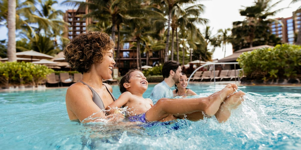 A family of 4 are all smiles while enjoying time in the Waikolohe pool at Aulani Resort