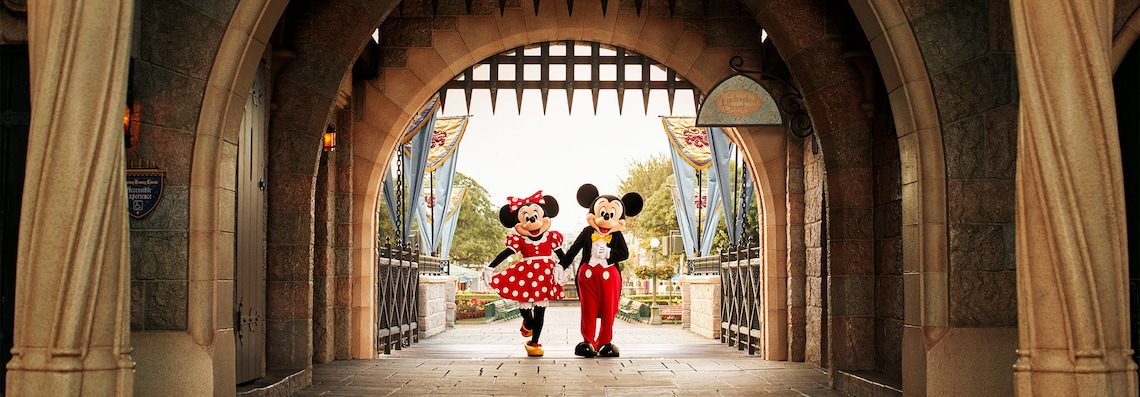Mickey and Minnie hold hands and smile at a magical castle.