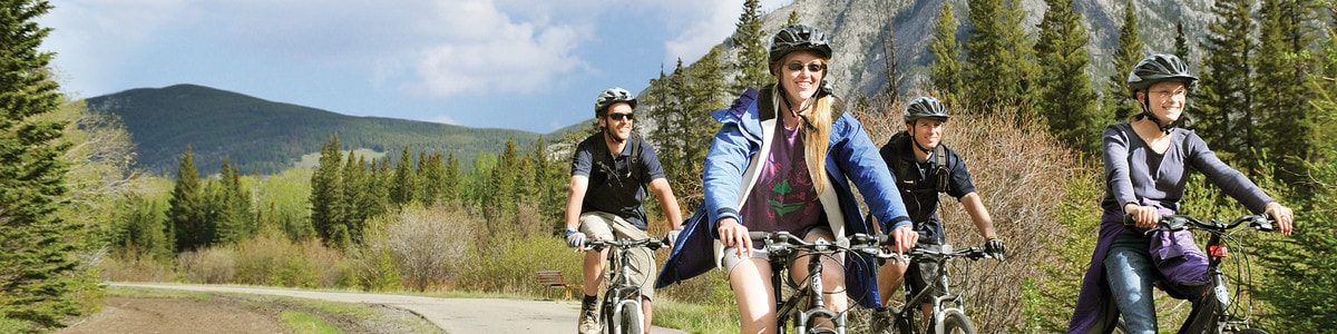 A group of tourists ride bikes along a mountain trail