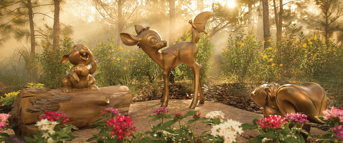 A wooded outdoor area with statues of Bambi, Thumper and Flower from the film 'Bambi'