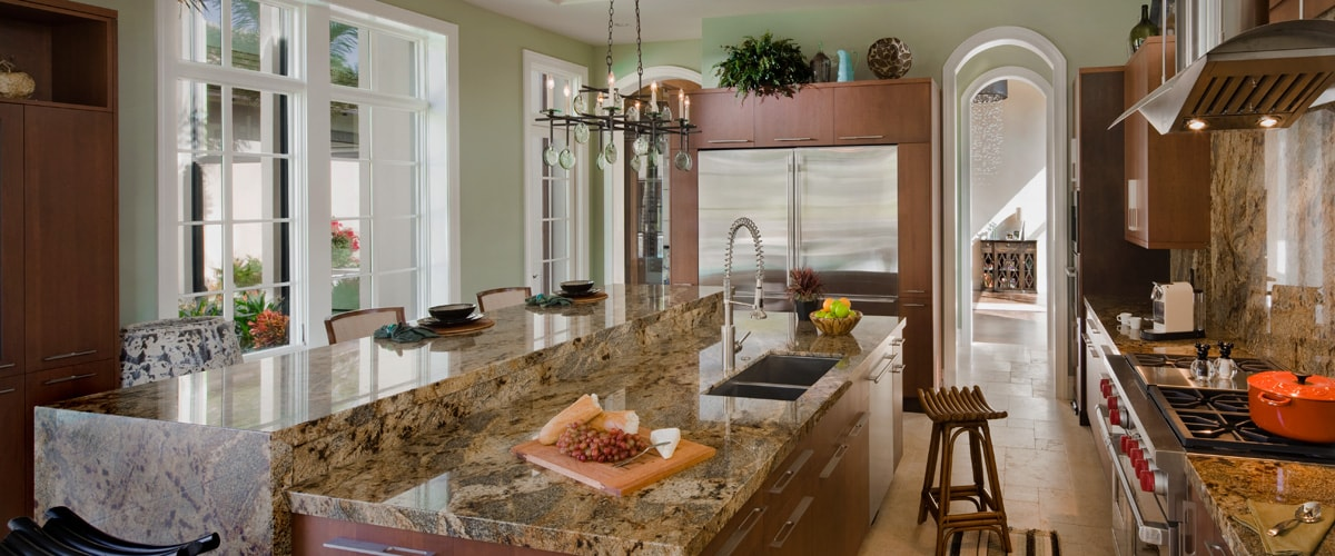 A large kitchen with a breakfast bar, range and arched doorways