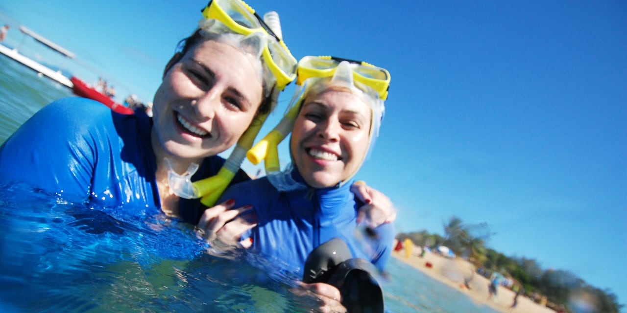 2 smiling teenage girls dressed in wet suits tread water and hold snorkel gear