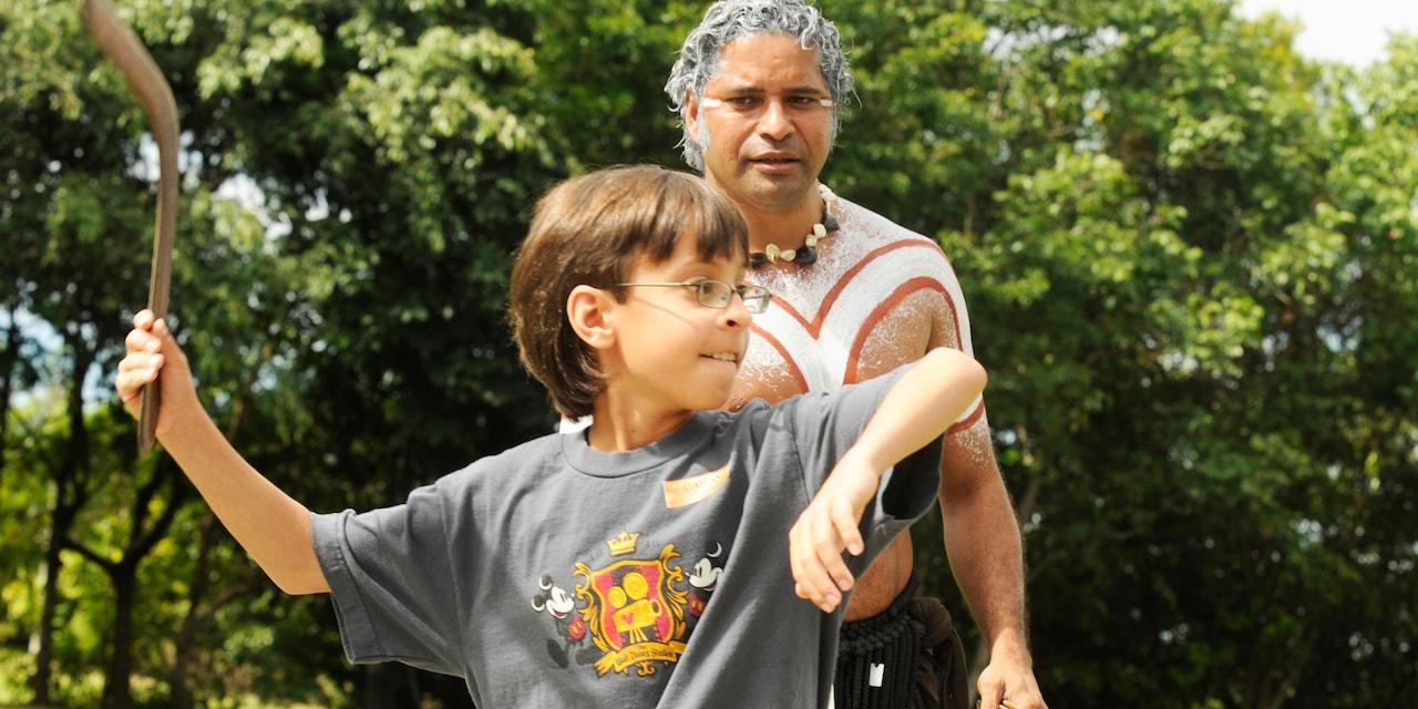 An aboriginal watches a boy throw a boomerang