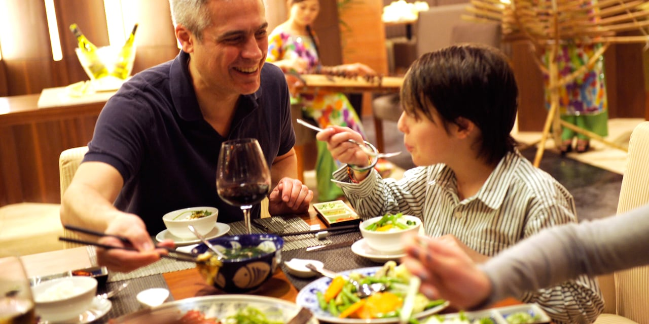 A boy blows on his hot soup to cool it as his father eats from a bowl with chopsticks