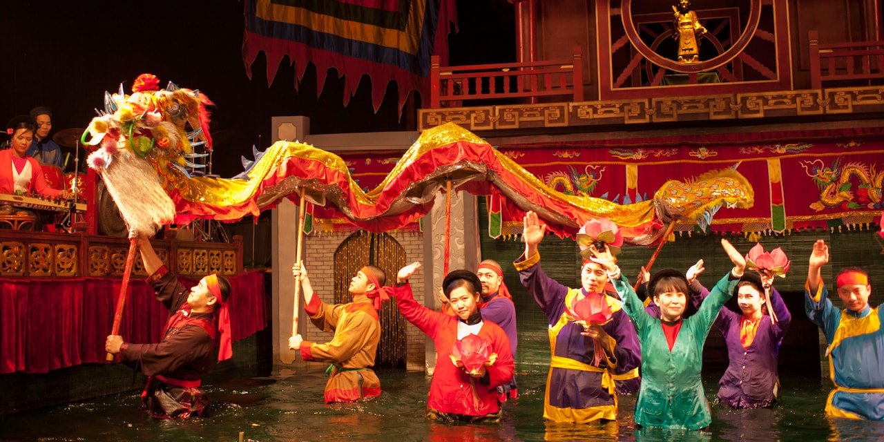 Costumed performers walk through a river carrying a long dragon puppet