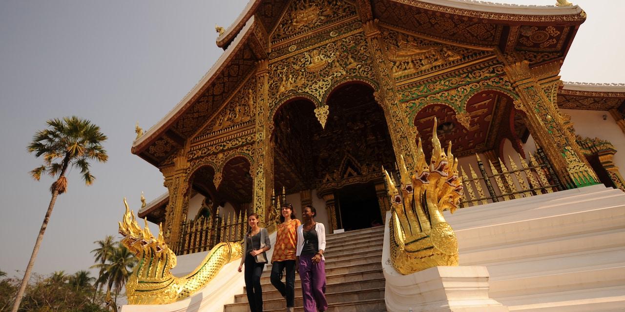 3 teenage girls walk down the steps of an ornate building