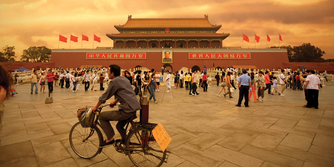 A man on a bicycle and dozens of tourists gather outside the Forbidden City