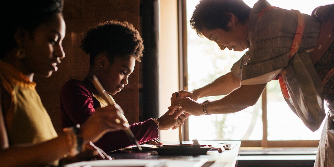 Two people learn calligraphy from a Japanese woman