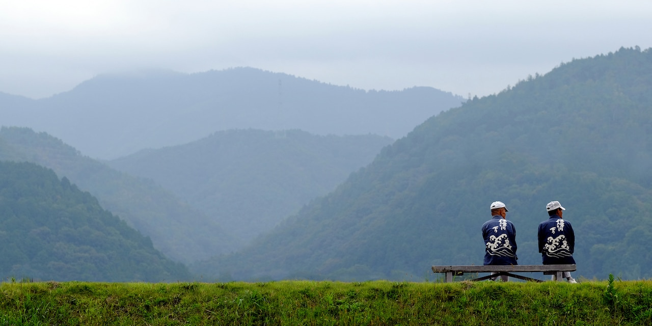 Two men in matching hats and shirts sit on a bench looking out at nearby hills