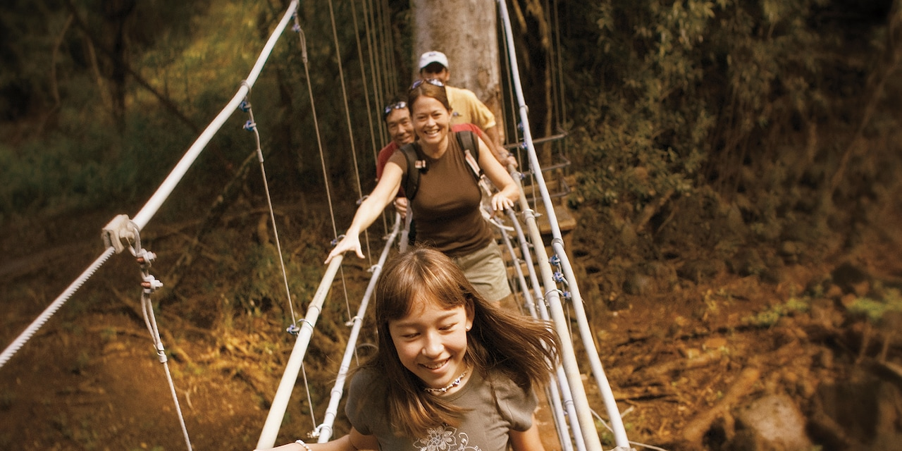 A family of 4 and an Adventure Guide walk across a hanging bridge in the forest