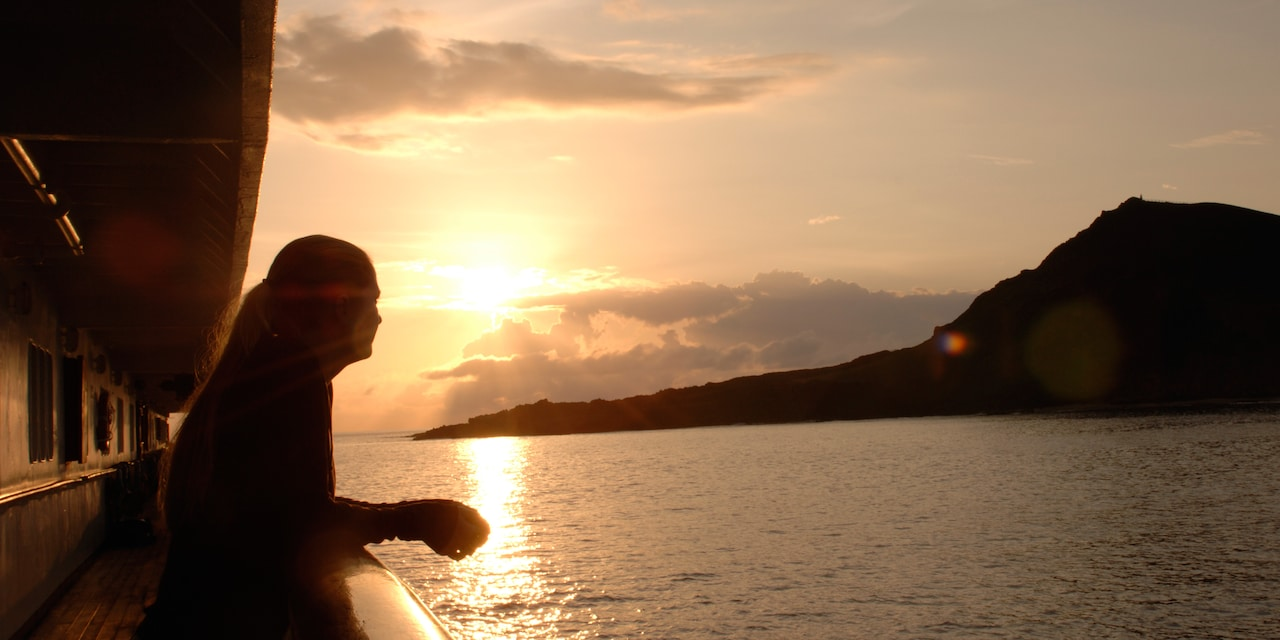A woman stands on the deck of a ship, looking out at one of the Galapagos Islands at sunset