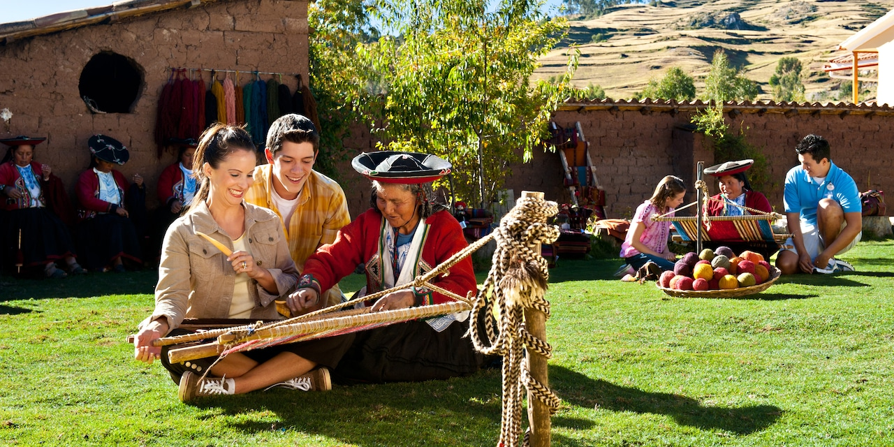 A Peruvian weaver teaches a mom and son to use a loom