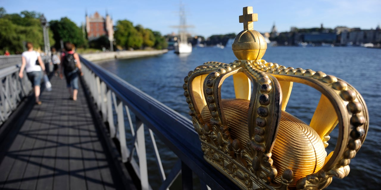 A gilded crown rests atop the railing of a bridge that spans a body of water