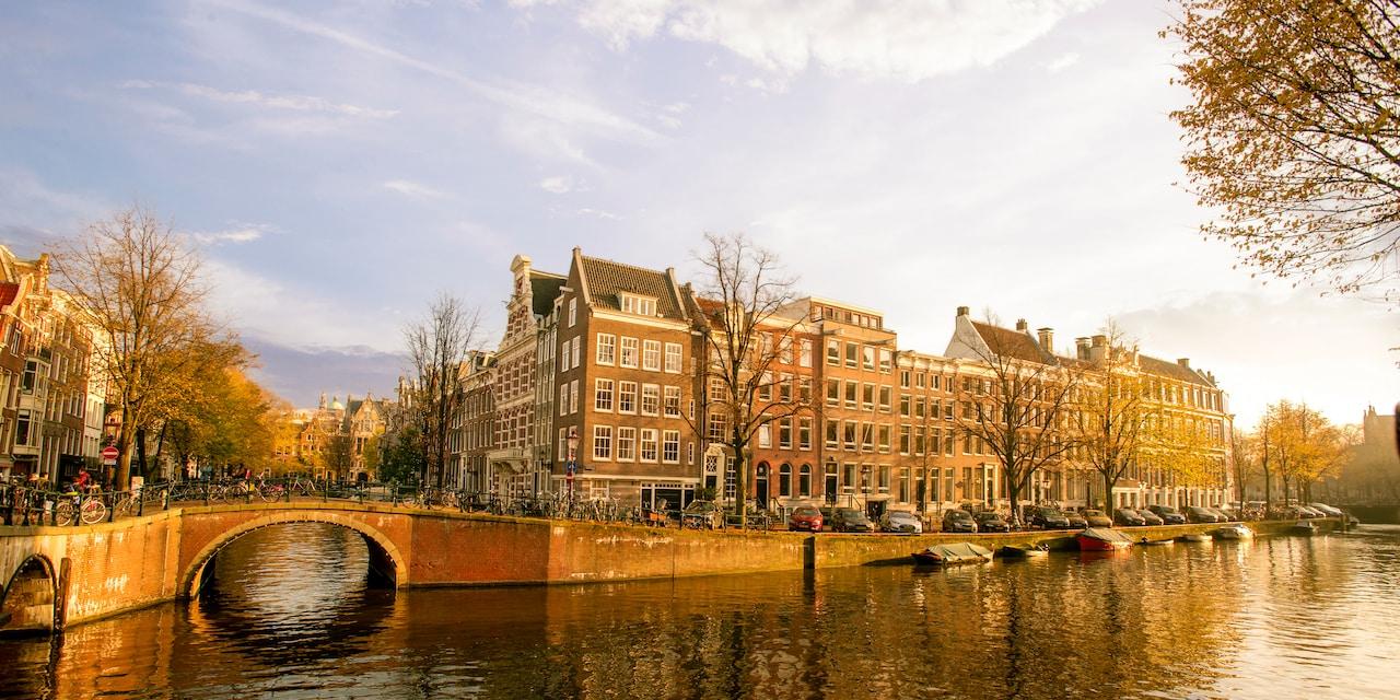 A stone pedestrian bridge on a river flanked by European buildings