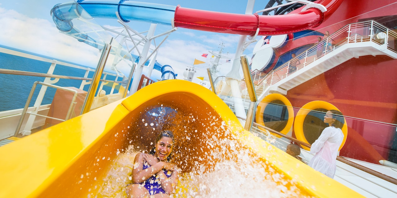 A woman slides down the AquaDuck water slide on the Disney Magic® Cruise Ship