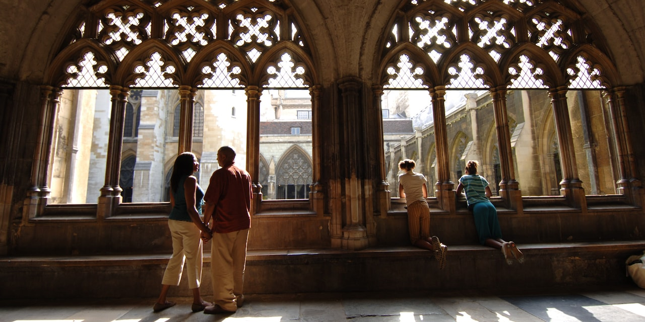 A family looks out a pair of windows at Westminster Abbey