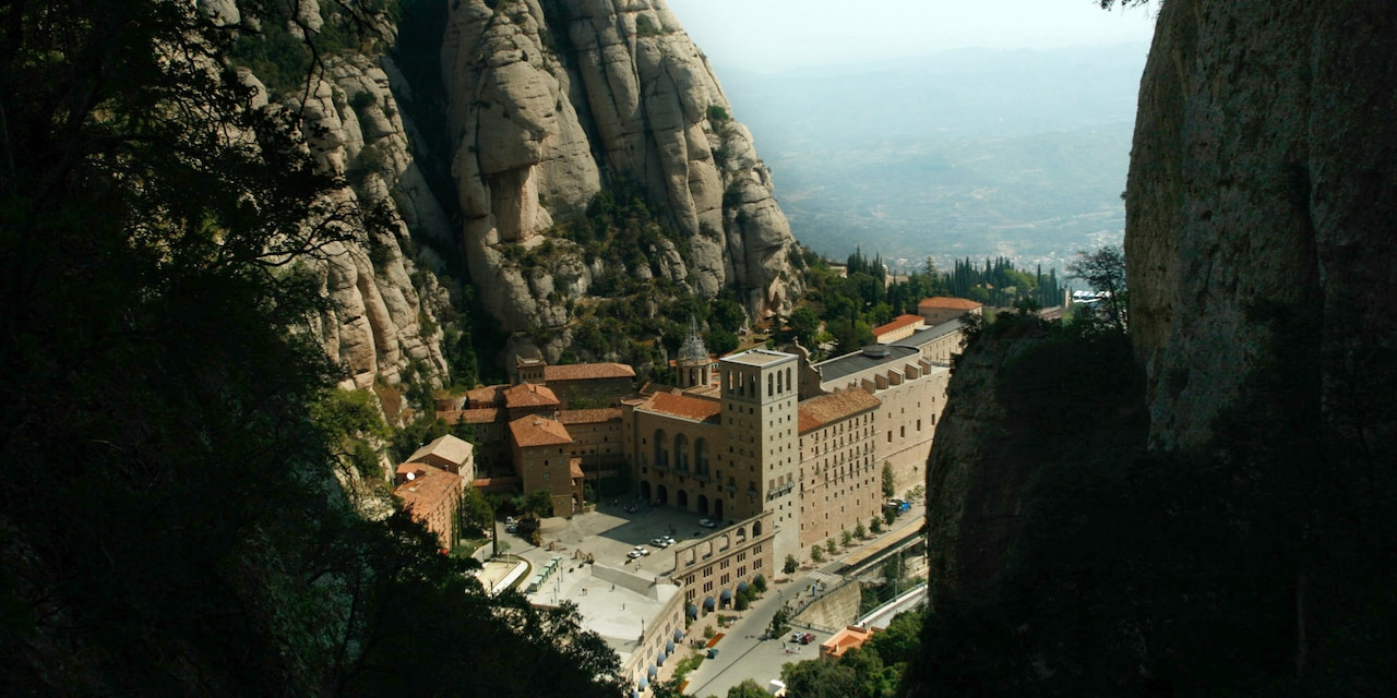 A monastery on a cliff side overlooking an ocean