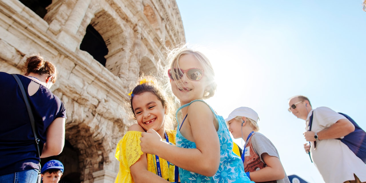 Two girls smile in front of a section of the Colosseum in Rome