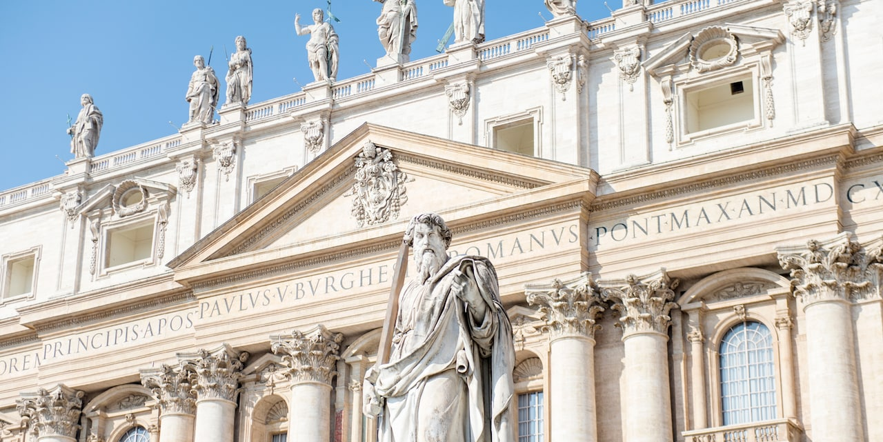 A statue of St. Paul stands in front of St. Peter's Basilica in Vatican Citype