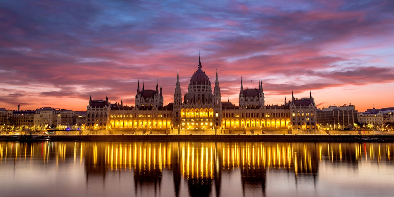The Budapest Parliament building at sunset, with reflections of its lights on the Danube River