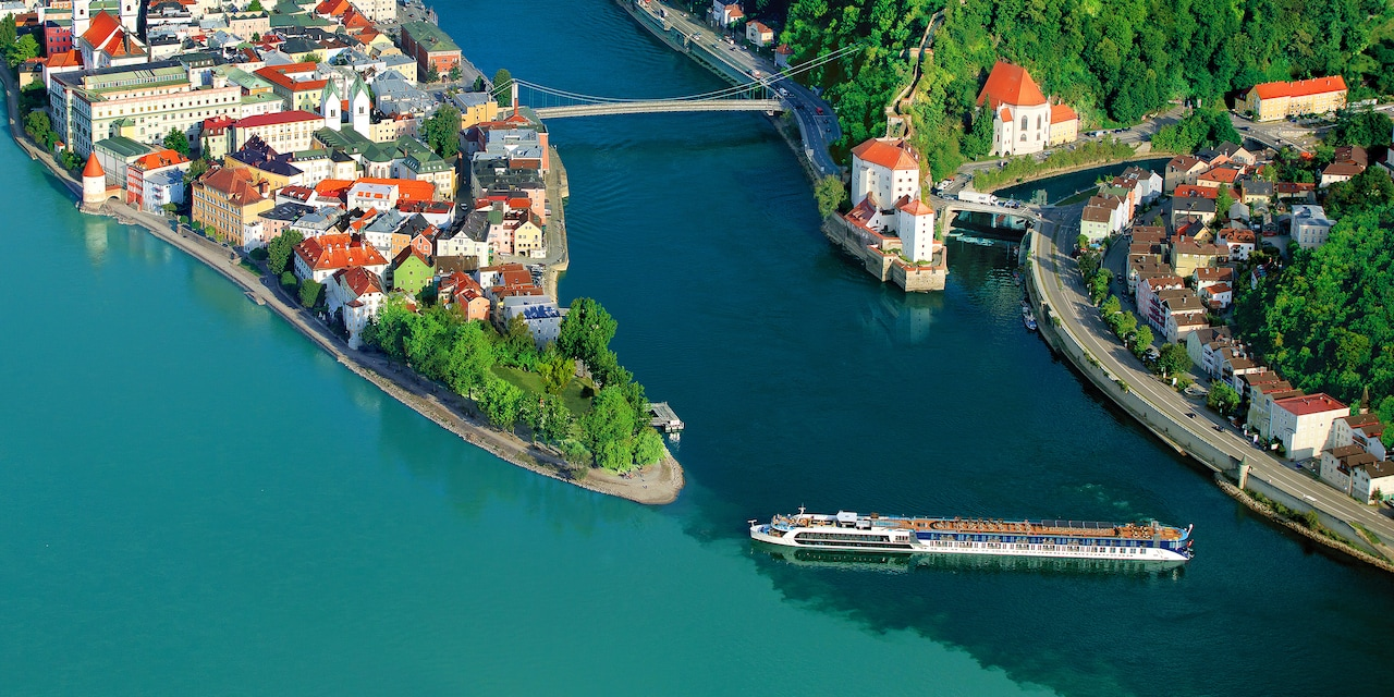 An AmaWaterways ship cruises down the Danube River near shores housing beautiful, quaint towns