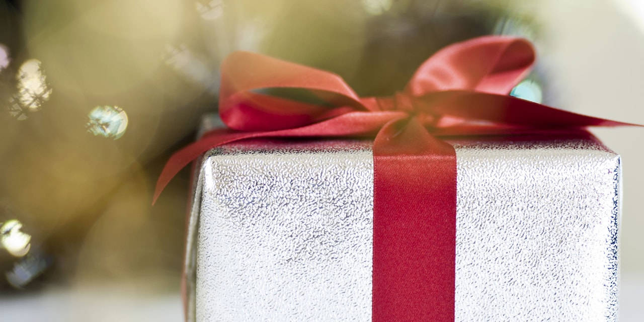 A Christmas present wrapped in paper and tied with a wide silk ribbon