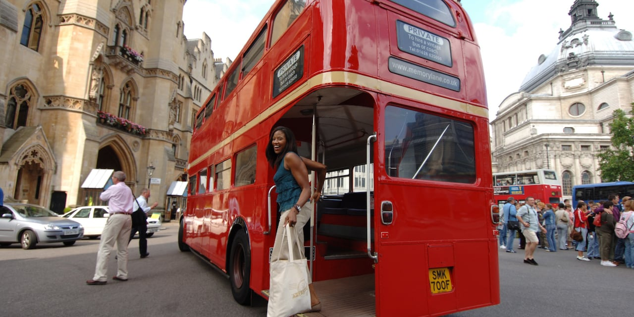 A woman steps off a double decker bus