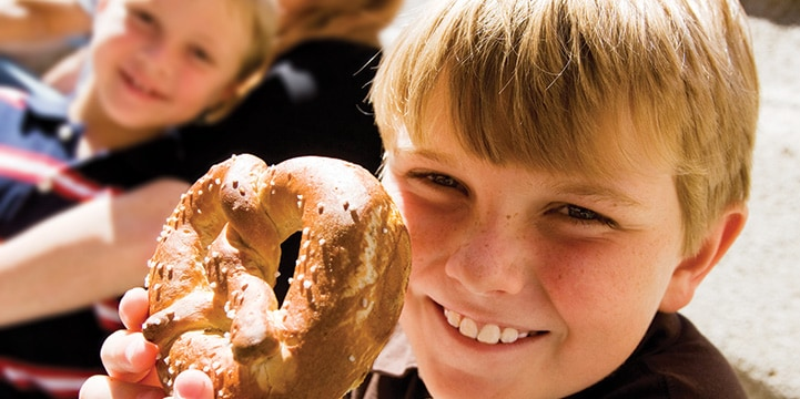 A smiling boy holds a large pretzel