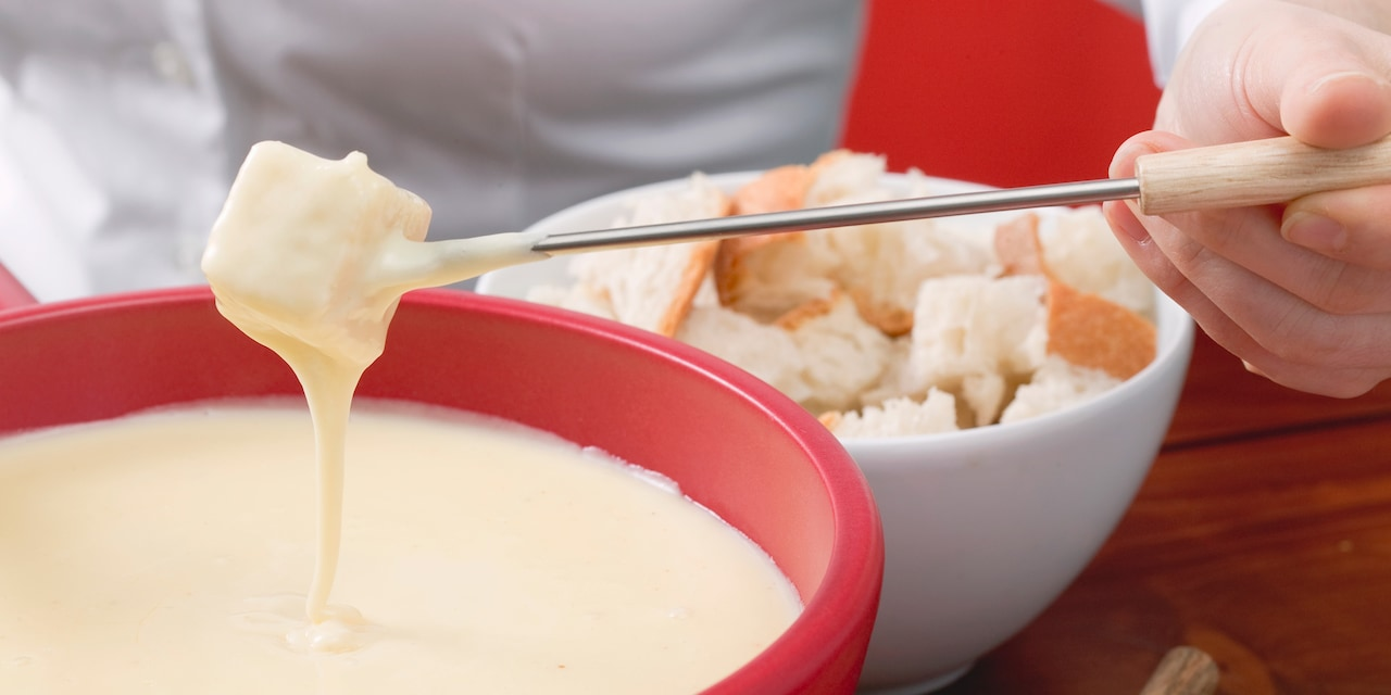 A man's hand holds a cube of bread on a long fondue fork that he dips into a bowl of fondue