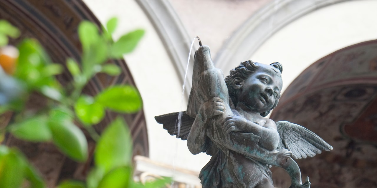 A winged cherub fountain sprays water