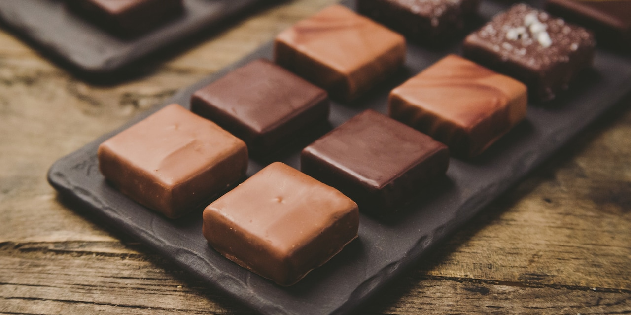 An assortment of 8 pieces of chocolate sits on a tray