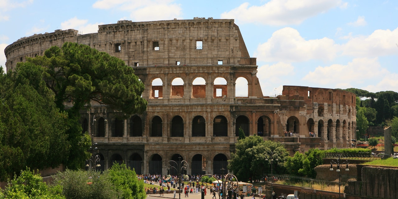 Tourists stand in the park surrounding the Colosseum