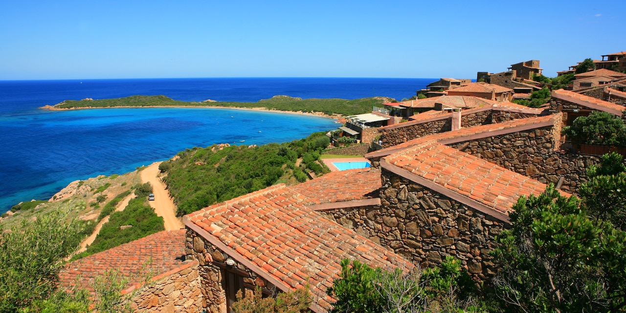 Tile rooftops and stone fences above the coast of a shrub covered beach