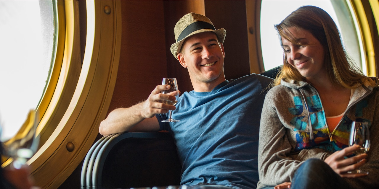 A couple drinks cocktails onboard a ship